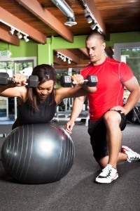 Personal trainer with woman holding dumbbells on fitness ball