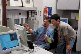 Software engineers talking and looking at computer screen
