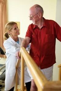 Occupational therapist helping senior man walk up stairs