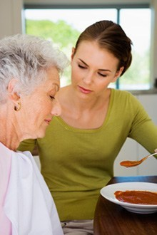 Woman helping an older woman eat soup