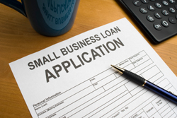 Application for small business loan on desk with pen