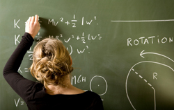 Student working on math problem on blackboard