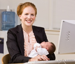 Businesswoman holding a baby