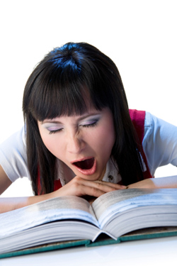 Female student yawning while reading a textbook