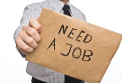 man holding need a job sign