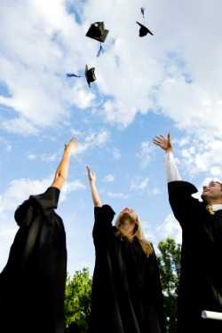 students throwing hats in air after graduating