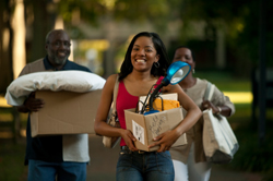 Young woman moving into college dorm with parents carrying boxes behind her