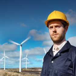 Close up of man wearing hard hat with wind turbines in background