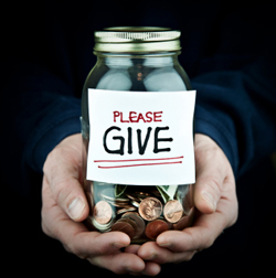 Man holding money jar with sticker on it that reads 'please give'