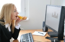 Businesswoman eating pizza at office desk