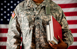 Soldier in military fatigues and carrying books