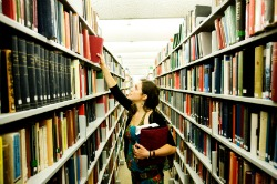 girl in library picking book off shelf