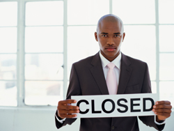 Serious-looking business man holding closed sign