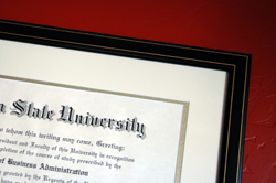 State university degree framed and hanging on wall