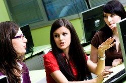 three students looking at training programs on computer