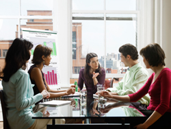 Five business people in a meeting, four of which are women