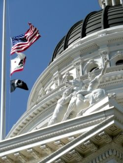 california state capitol building with flags blowing in wind