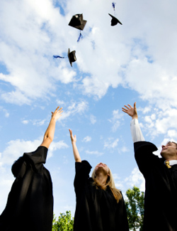 Three graduates throw hats into the air