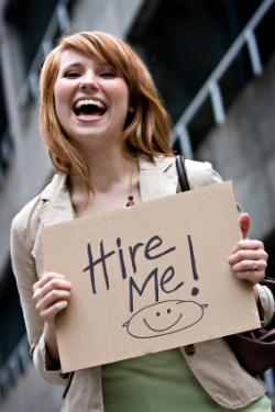 woman smiling with hire me sign