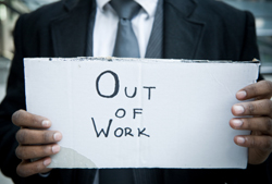 Close up of business man holding an 'Out of Work' sign