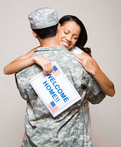Woman hugging soldier and holding welcome home sign