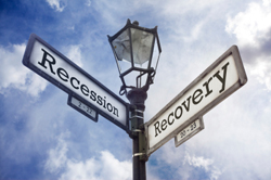 Crossroad signs saying recession and recovery