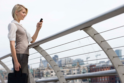 Business woman standing outside, looking at cell phone with view of city in the background