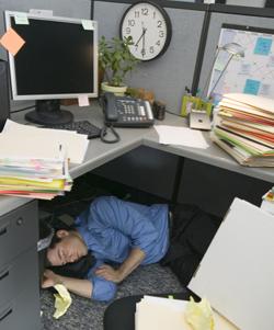 Man Sleeping Under Desk At Work