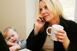Woman at home on work-related call with son next to her
