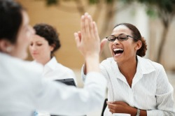 Businesswomen high fiving in meeting