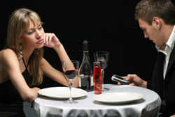 Man checking messages on cell phone while on a date with a woman