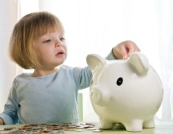 Little girl putting money in piggy bank