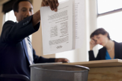 Businessman Throwing Away a Stack of Resumes