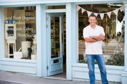 Business owner standing in front of store
