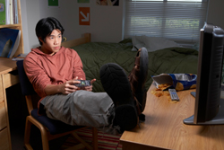 Male college student playing video games in dorm room