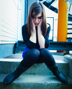 Sad young woman sitting on steps alone